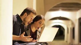 Förvånade par som finner innehållet på bärbara datorn i natten lager videofilmer