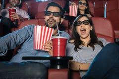 Förvånade par som håller ögonen på en film 3d Arkivbilder