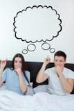Förvånade par som visar upp på det tomma copyspaceställemolnet Arkivfoto