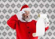 Förvånade Santa Claus som ser önskelistan Arkivbilder