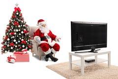 Förvånade Santa Claus som sitter i en fåtölj och en hållande ögonen på TV royaltyfria foton