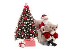 Förvånade Santa Claus som sitter i en fåtölj och läser en newsp arkivfoton