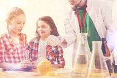 Förvånade ungar som håller ögonen på deras lärare göra experiment på skolalabbet arkivfoto