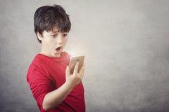 Förvånat barn med en mobiltelefon Royaltyfria Foton
