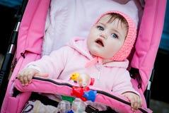Förvånat behandla som ett barn flickan i sittvagn Arkivfoton