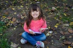 Förvånat gulligt barn i glasögon och att skriva i anteckningsbok genom att använda blyertspennan som ler arkivfoto