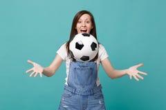 Förvånat roligt fotbollsfanjubel för ung kvinna upp det favorit- laget för service som kastar fotbollbollen som isoleras på blå t arkivfoto