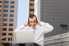Förvånat sammanträde för affärsman på moment med bärbar datorbärtråg för murbruk hans hea arkivfoto