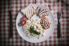 Förvanskad ägg och bacon på plattan arkivfoto