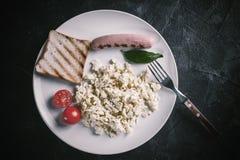 Förvanskad ägg och korv på plattan arkivfoto