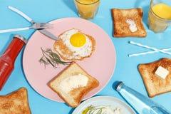 Förvanskade ägg, bredde smör på rostade bröd och drinkar på en blå tabell Bästa sikt för frukost royaltyfri foto