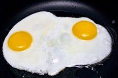 Förvanskade ägg i olja i en stekpanna royaltyfria bilder