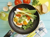 Förvanskade ägg, kök för stekpannamorgonmat som är traditionellt på en träbakgrund Arkivbild