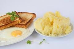 Förvanskade ägg med örter och rostade bröd på det vita porslinet pläterar, mosade potatisar Fotografering för Bildbyråer