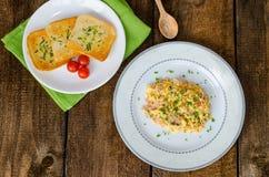 Förvanskade ägg med gräslöken och bacon, rostat bröd med örter Royaltyfri Bild