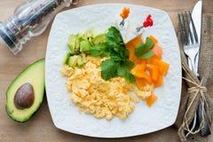Förvanskade ägg med grön och orange paprika och avokadot Royaltyfri Bild