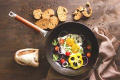Förvanskade ägg med grönsaker i en kastrull royaltyfri bild