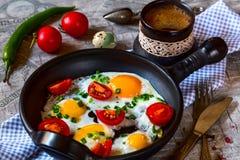 Förvanskade ägg med tomater i en panna på en grå tabell Royaltyfria Bilder