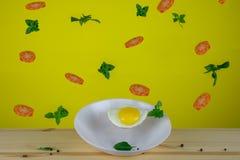Förvanskade ägg och tomater med basilika royaltyfri foto