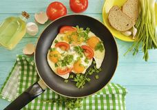 Förvanskade ägg, stekpannamorgonkök som är traditionellt på en träbakgrund Arkivfoton