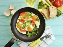 Förvanskade ägg, stekpannamorgonmat som äter kokkonstkök som är traditionellt på en träbakgrund Royaltyfri Foto
