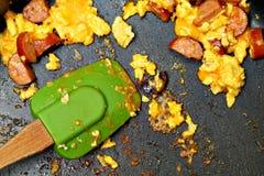 Förvanskat ägg, ost, korvrester i panna Royaltyfria Bilder