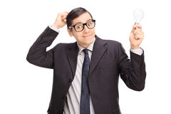 Förvirrad affärsman som rymmer en ljus kula Arkivbild