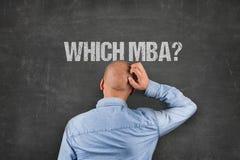 Förvirrad affärsmanScratching Head Under MBA text på svart tavla Fotografering för Bildbyråer