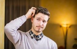 Förvirrad eller tvivelaktigt ung man som skrapar hans huvud och ser upp royaltyfri foto
