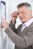 Förvirrad hög man med demens som ser väggkalendern Royaltyfri Foto