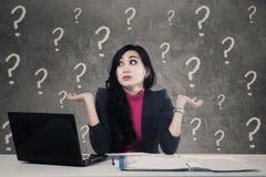 Förvirrad kvinna med frågefläckar i regeringsställning royaltyfri fotografi