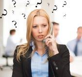 Förvirrad kvinna med telefonen i regeringsställning Arkivbild