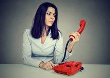 Förvirrad kvinnahäleridåliga nyheter över telefonen royaltyfria foton