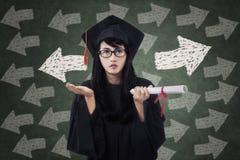 Förvirrad kvinnlig student i avläggande av examenkappa Royaltyfri Foto