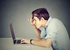 Förvirrad man med bärbara datorn på grå färger arkivfoton