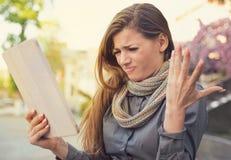 Förvirrad olycklig kvinna med den brutna minnestavlan arkivfoto