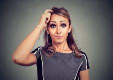 Förvirrad rolig seende kvinna som skrapar huvudet Arkivfoton