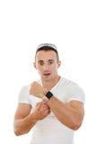 Förvirrad stilig man i den vita t-skjortan som pekar ett finger på cloc Arkivfoton