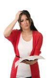 Förvirrad student som läser en bok Royaltyfria Bilder