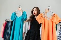 Förvirrad ung kvinna som väljer mellan två klänningar Arkivfoto