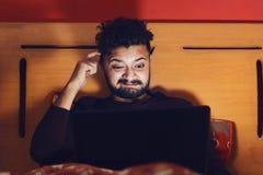 Förvirrad ung man som ser bärbara datorn och tänker i mörker royaltyfri bild