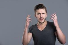 Förvirrad ung skäggig manöppningsmun och lyftahänder arkivbilder
