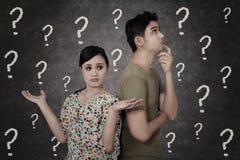 Förvirrade par med frågefläckar på svart tavla Arkivfoton