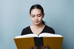 Förvirrat kvinnligt tonårigt läsa en textbok royaltyfria bilder