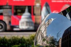 Förvriden reflexion av domkyrkan för St Paul ` s, reflekterad i yttersida av spegelskulptur Suddig röd London buss i bakgrund royaltyfri fotografi