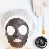Föryngring och skincare i brunnsortsalong med gyttjaframsidamaskeringen Royaltyfri Foto
