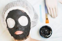 Föryngring och skincare i brunnsortsalong med gyttjaframsidamaskeringen Royaltyfri Bild
