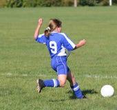 Fútbol adolescente de la juventud que golpea la bola con el pie Imagenes de archivo