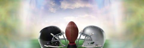 Fútbol americano contra cascos del equipo con la bola con la transición del cielo Imágenes de archivo libres de regalías