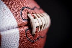 Fútbol americano de cuero en fondo negro Imagen de archivo